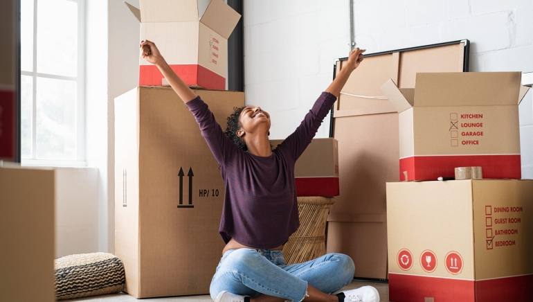 Happy young woman sitting in new apartment and raising arms in joy after moving in. Joyful and excited african girl moving to new home. Black woman sitting on floor in her house.